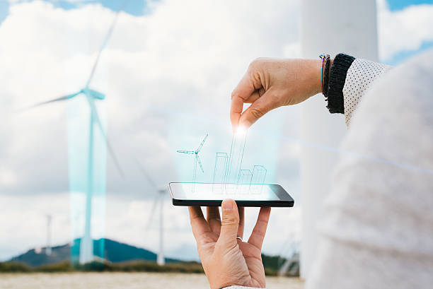 Engineer woman increasing wind energy production with hologram on phone stock photo