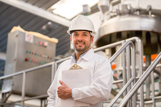 Engineer working at a factory Latin American engineer working at a factory wearing a helmet and holding a clipboard food warehouse stock pictures, royalty-free photos & images
