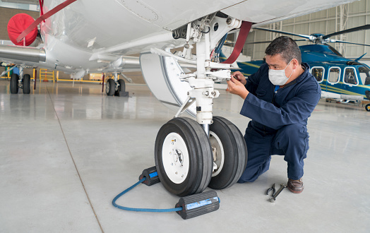 Engineer working at the airport wearing a facemask while fixing an airplane's landing gear