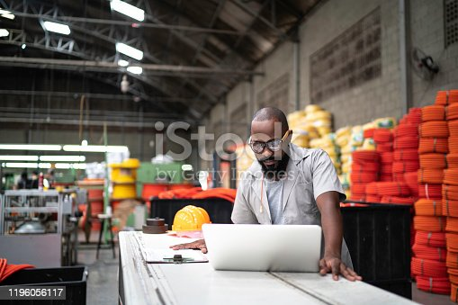 Engineer working at the factory using laptop