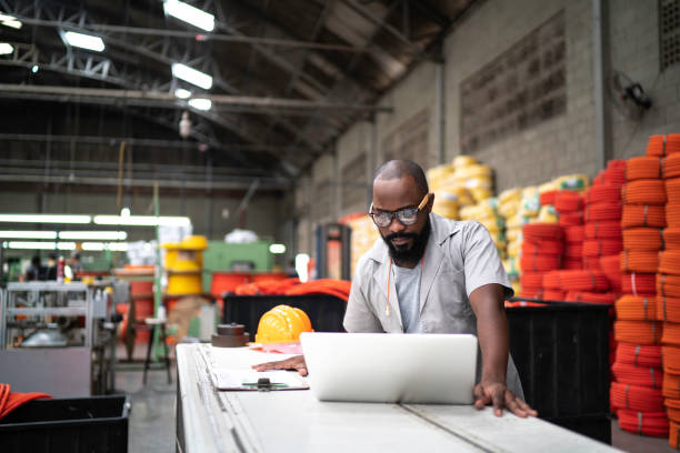 Engineer working at the factory using laptop stock photo