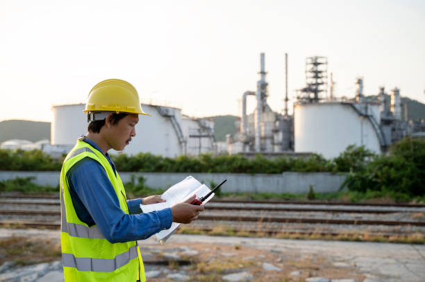 Engineer working in a oil refinery with talking stock photo
