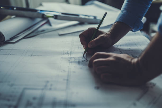 Engineer working late Hand drawing on a blueprint engineering stock pictures, royalty-free photos & images