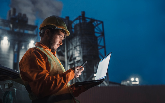 Side view of engineer working nightshift and using technology in front of petroleum industrial factory and using laptop and smart phone.