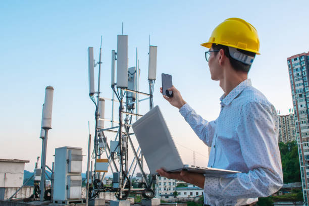 Engineer working on a laptop and phone,Checking the communications tower stock photo