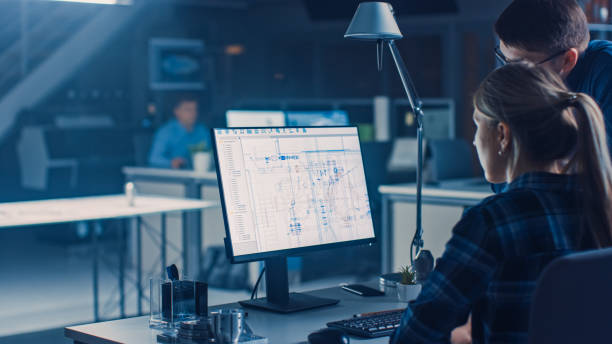 Ingenieur am Desktop-Computer, Bildschirm zeigt CAD-Software mit technischen Blaupausen, ihr männlicher Projektmanager erklärt Die Berufsspezifikationen. Büro für Industrial Design Engineering Facility – Foto