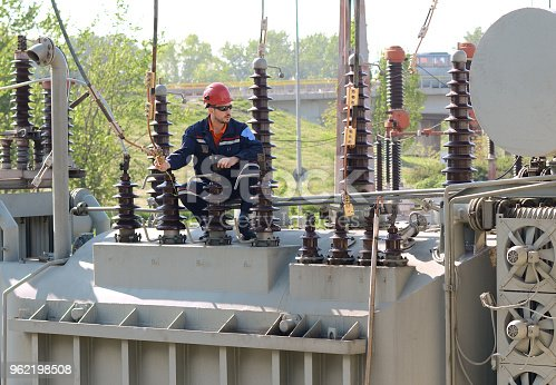 Electrician and electricity transformer. Checking equipment.