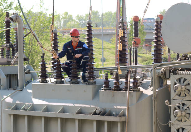 engineer working on high voltage transformer in electricity substation. - transformers stock photos and pictures