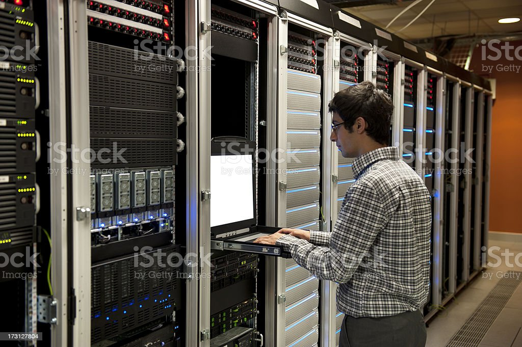 IT engineer working on server in data center This IT engineer stands facing a rack of servers stretching from the near-left corner to a distant rust-colored wall.  He is wearing a plaid shirt with khakis.  His hands are on a keyboard attached to the center of the server rack to configure the servers in this data center. Adult Stock Photo