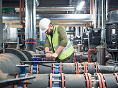 Engineer working on valve in factory or utility