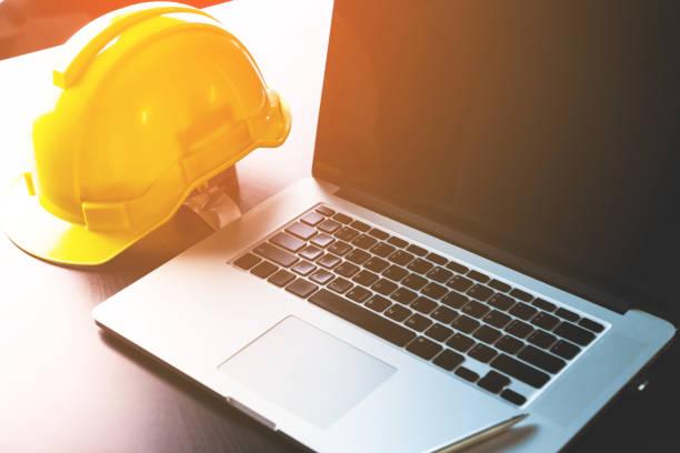 Mesa de trabajo de ingeniería con ordenador y casco de seguridad - foto de stock