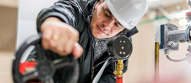 Engineer working while wearing a white hardhat stock photo