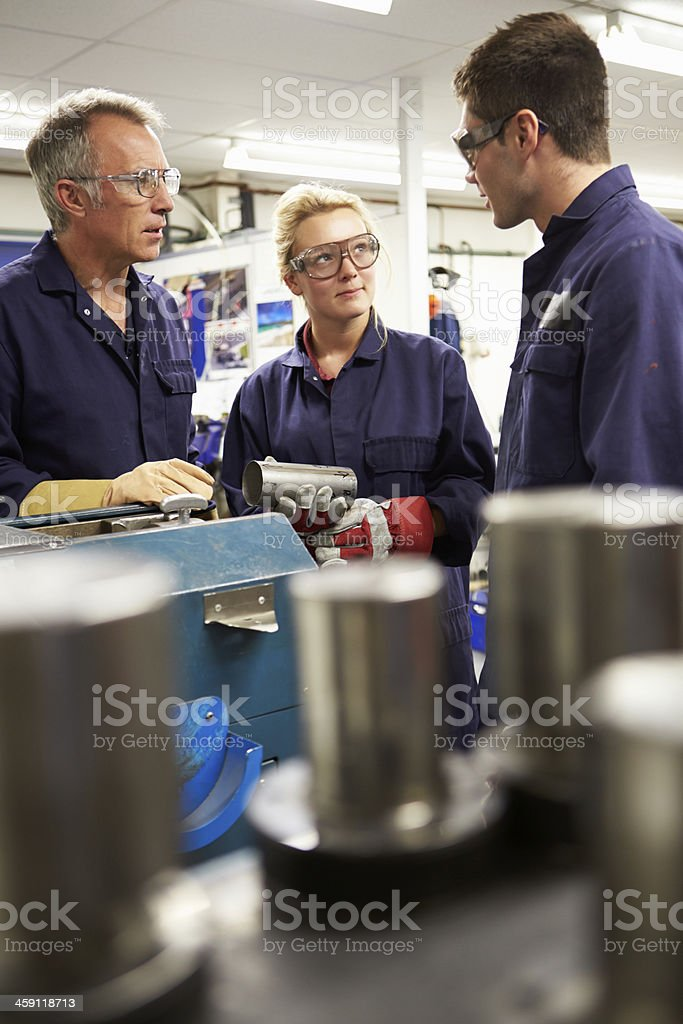 Engineer Working With Apprentices On Factory Floor stock photo