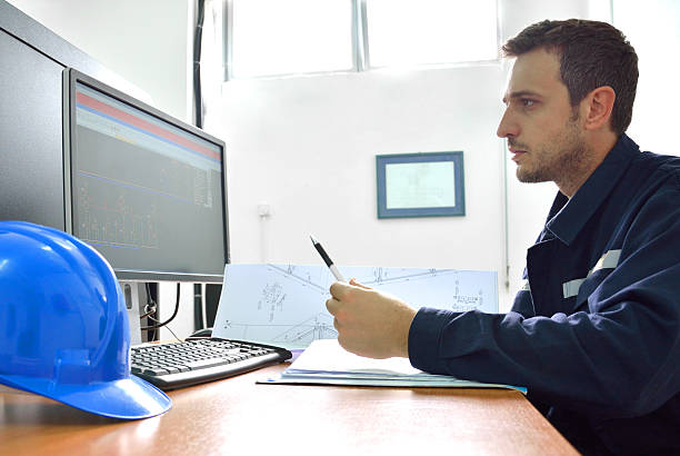 Engineer Working with Blueprints at the Desk – Foto