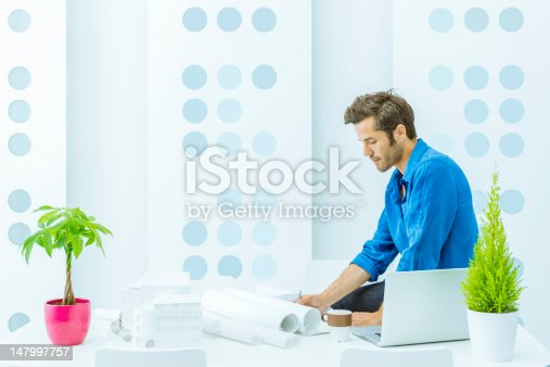 Engineer working with blueprints, in a contemporary design office.
