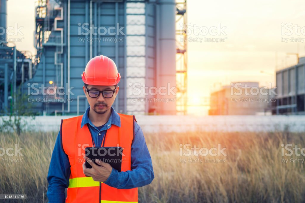 Engineer working with tablet PC near power plant