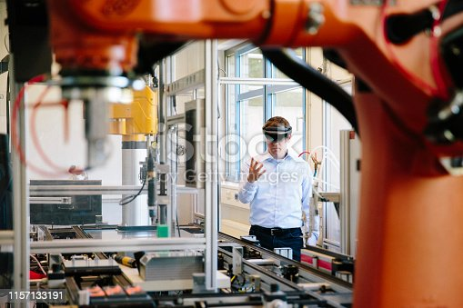 engineer works with a HoloLens place a virtual robotic arm into the production line
