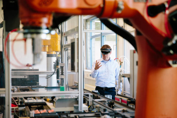 engineer works with a HoloLens: place a virtual robotic arm into the production line stock photo