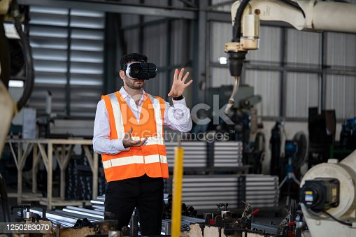 973144806 istock photo Engineer works with a HoloLens: place a virtual robotic arm into the production line 1250283070