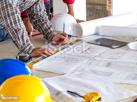 521012560istockphoto Engineer/architect/worker man discussing about building plan for construction at job site, working on desk/table with drawing/blueprint/business plan 962467062