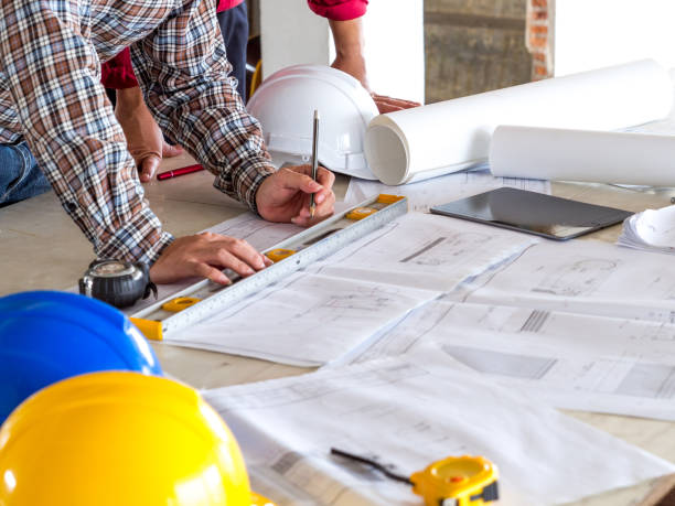 engineer/architect/worker man discussing about building plan for construction at job site, working on desk/table with drawing/blueprint/business plan - council flat stock photos and pictures
