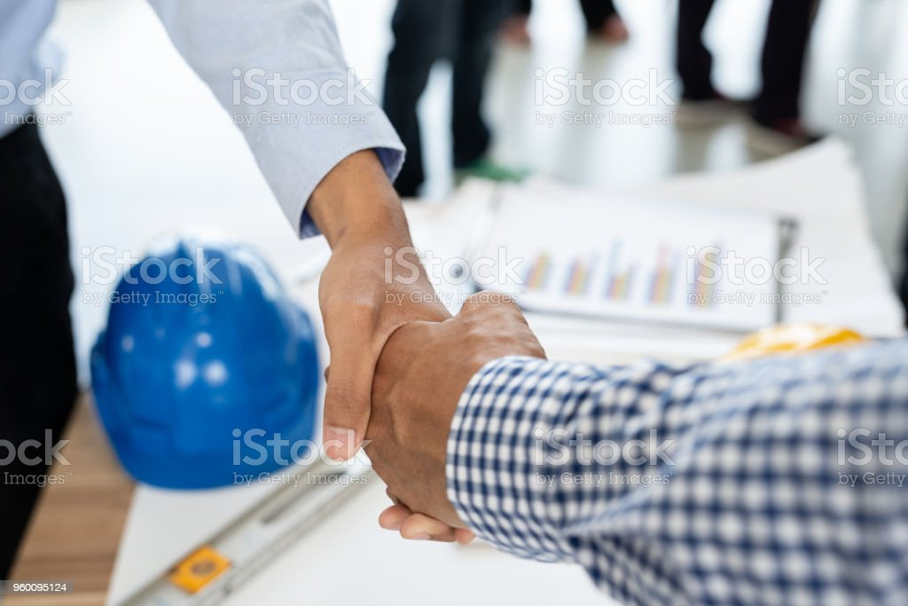 Engineering and businessman shaking hands after successful deal while working in the office center stock photo
