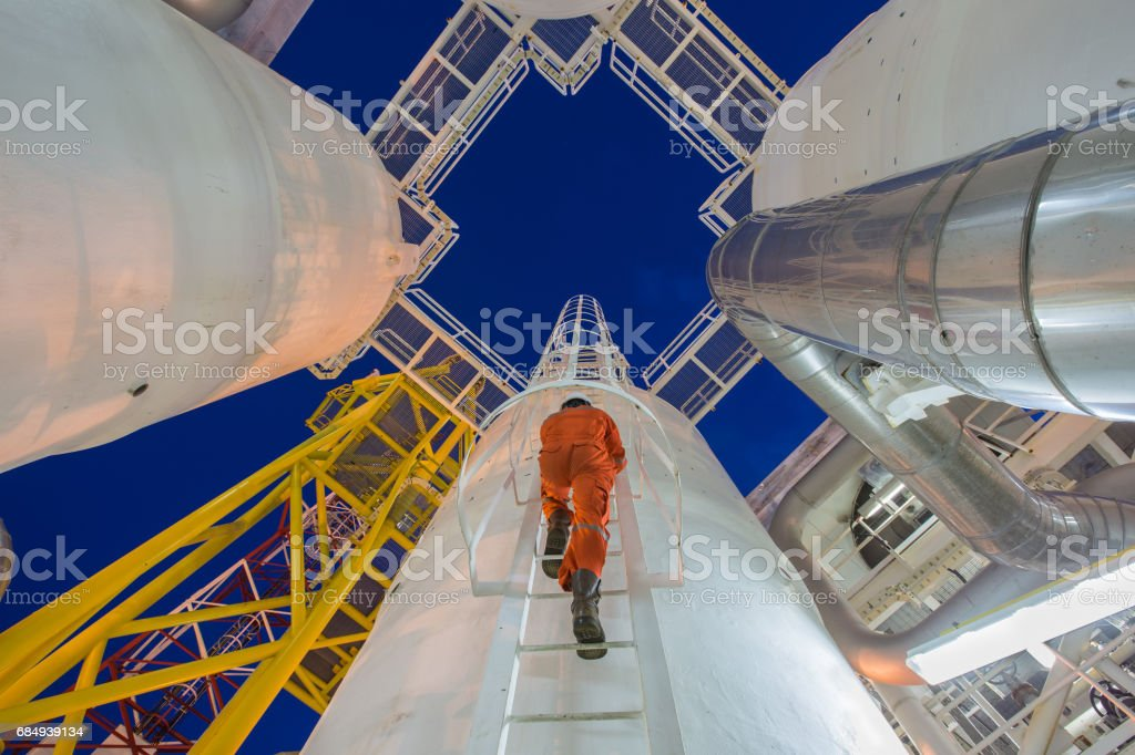 Engineering climb up to oil and gas process plant to observer gas dehydration processing in night shift stock photo