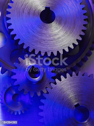 Engineering gears and cogs connecting on a stainless steel background. Blue lighting. Teamwork concept.Click on the link below to see more of my business images