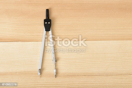 613651130 istock photo Engineering compass on a wooden surface in top view. 610952276