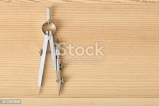613651130 istock photo Engineering compass on a wooden surface in top view. 612252806