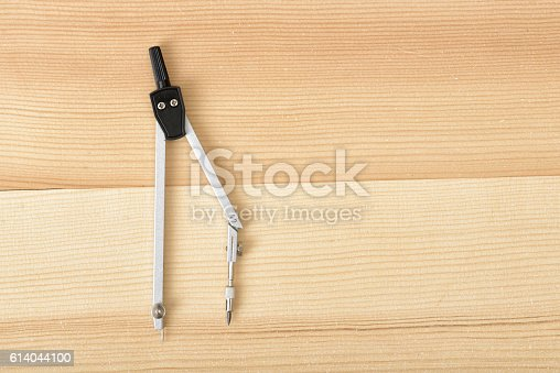 613651130 istock photo Engineering compass on a wooden surface in top view. 614044100