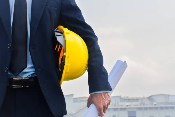 Engineering Construction holding yellow helmet blueprint at Construction background Engineering Construction holding yellow helmet blueprint at Construction background project manager stock pictures, royalty-free photos & images