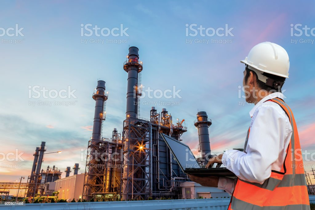 Engineering is use notebook check and standing in front of oil refinery building structure in heavy petrochemical industry royalty-free stock photo