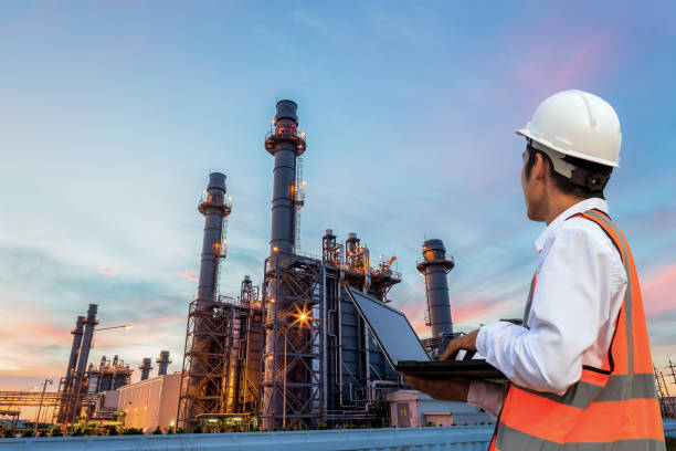 Engineering is use notebook check and standing in front of oil refinery building structure in heavy petrochemical industry stock photo