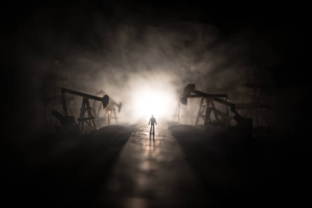 Engineering man standing against beautiful dusky sky of oil refinery plant. Silhouette of a man standing on the road at the oilfield. – zdjęcie
