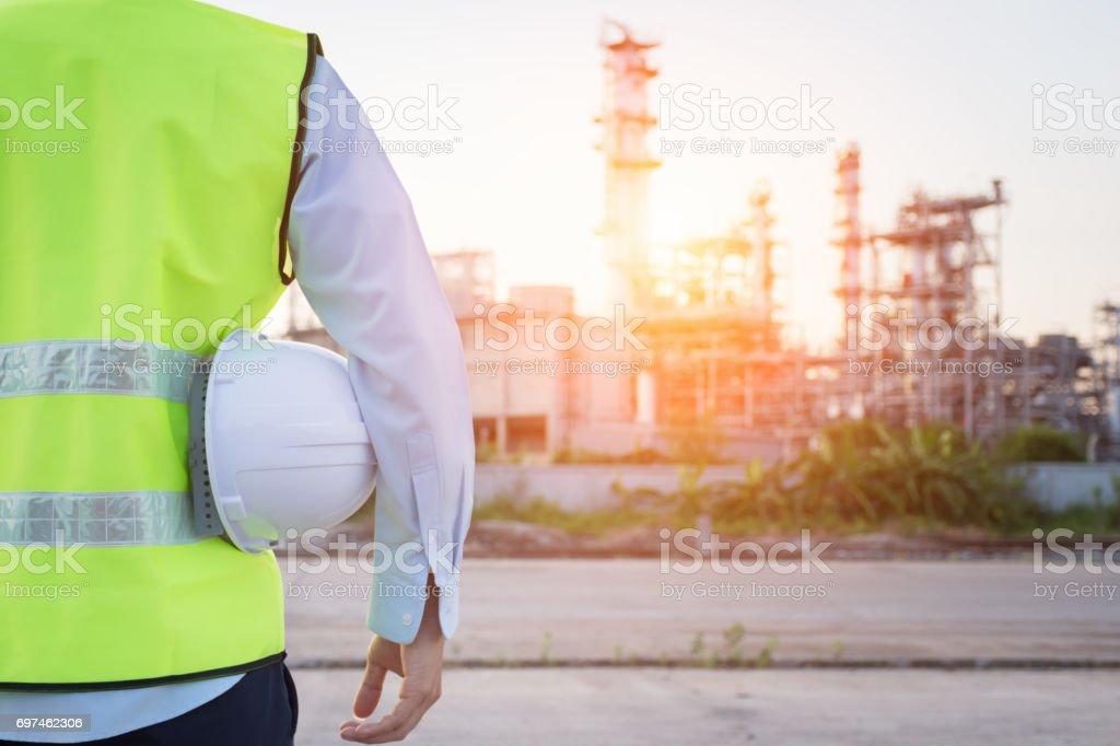 Hombre de ingeniería pie con casco de seguridad blanco cerca de la refinería de petróleo - Foto de stock de Accesorio de cabeza libre de derechos