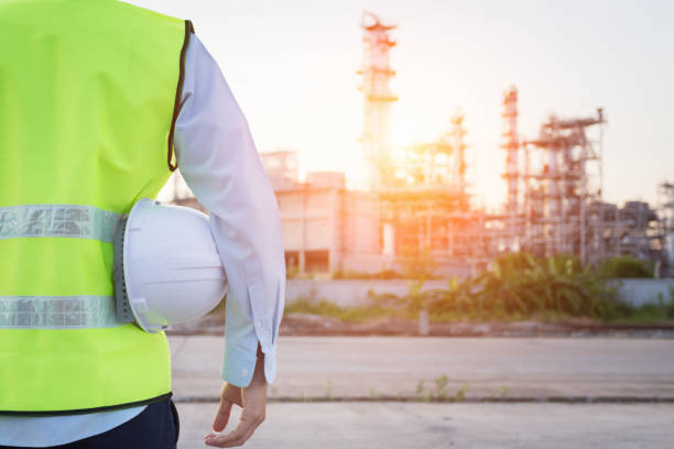engineering man standing with white safety helmet near to oil refinery - refinery stock photos and pictures