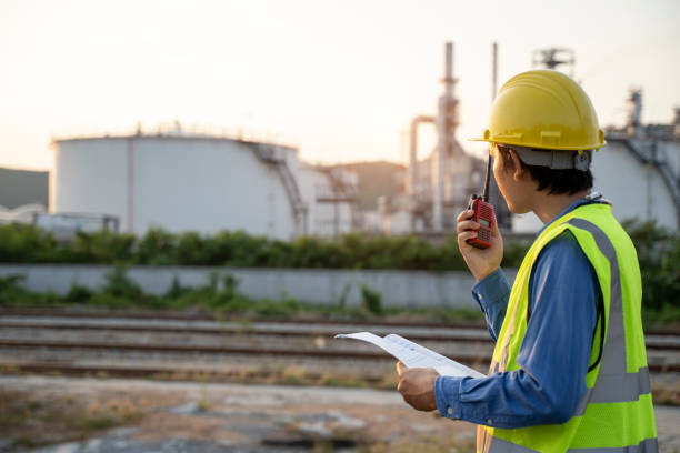 Engineering man with white safety helmet standing in front of oil refinery building structure in heavy petrochemical industry, Engineer with oil refinery industry plant background stock photo
