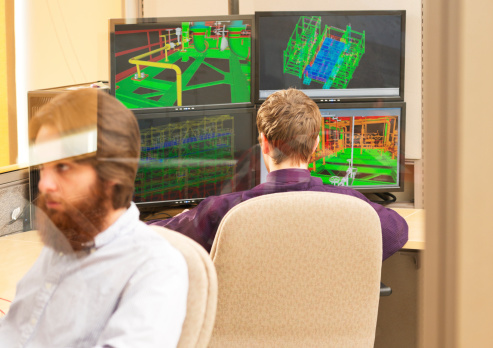 An Engineer 3D drafting in the office.  Limited Depth of field with focus on the engineer in the background