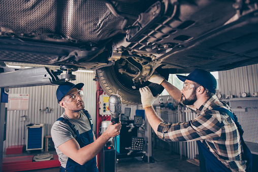 istock Engineering, protection, reliability, safety, oneness, colleagues, assistance. Professionals in blue overalls, protective spectacles are examining changing tires, tyres, brake pads at work shop 929108146