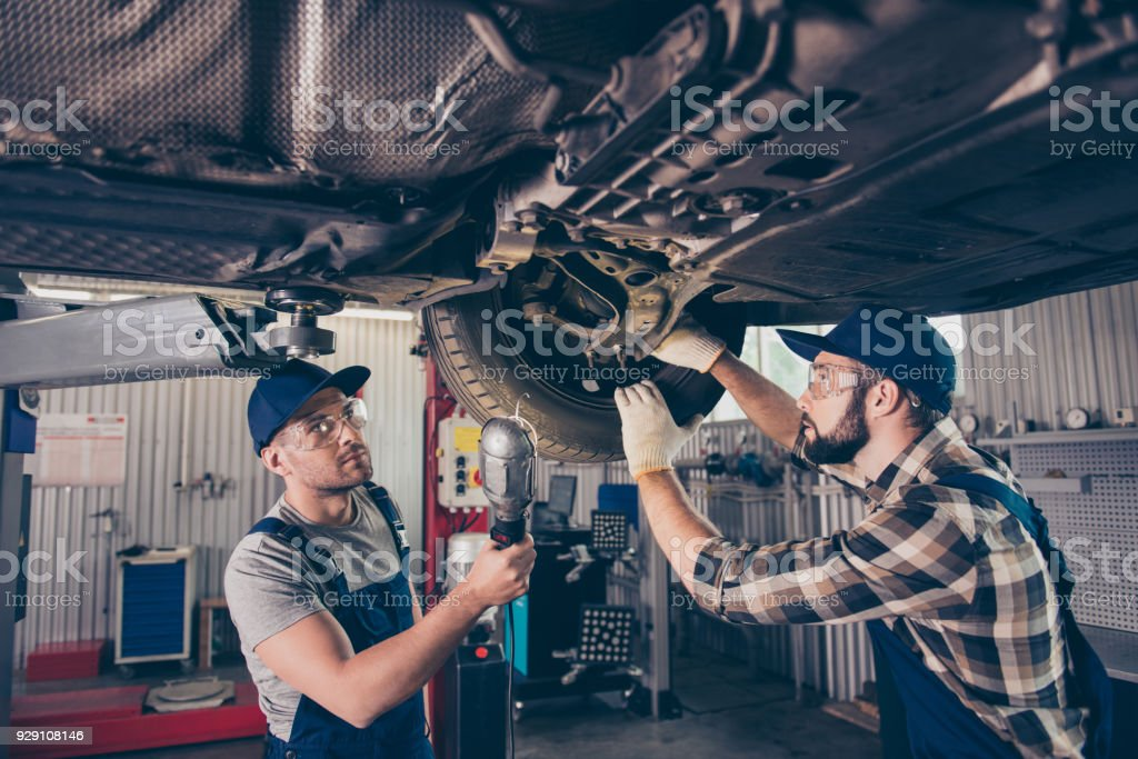 Engineering, protection, reliability, safety, oneness, colleagues, assistance. Professionals in blue overalls, protective spectacles are examining changing tires, tyres, brake pads at work shop stock photo