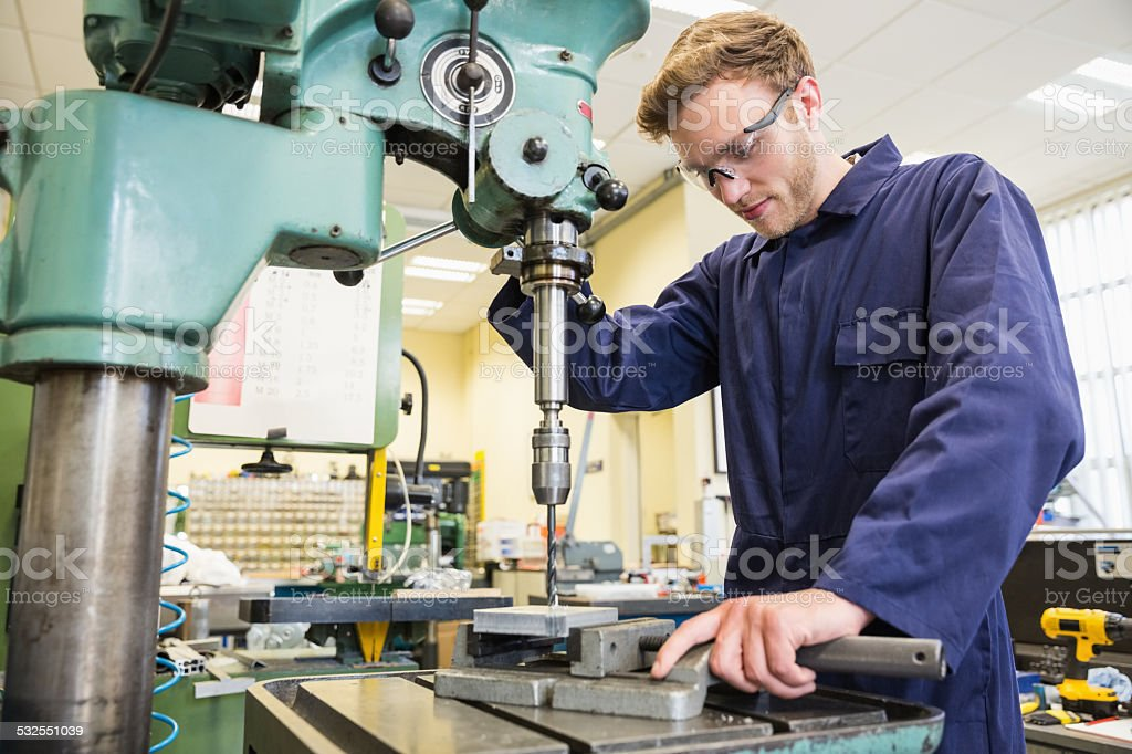 Engineering student using large drill royalty-free stock photo