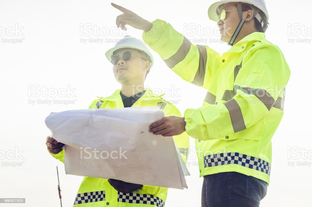 Asian engineers and technicians inspect and discuss at the wind power...
