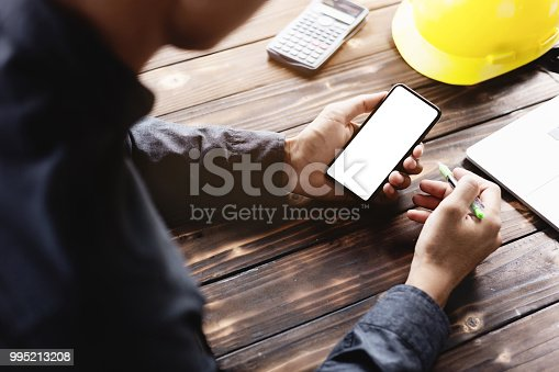 995213208 istock photo engineering using phone mobile on desk 995213208
