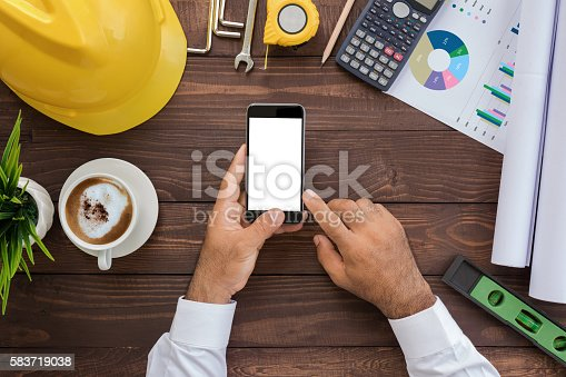 1134879628 istock photo engineering using phone on his workspace top view 583719038