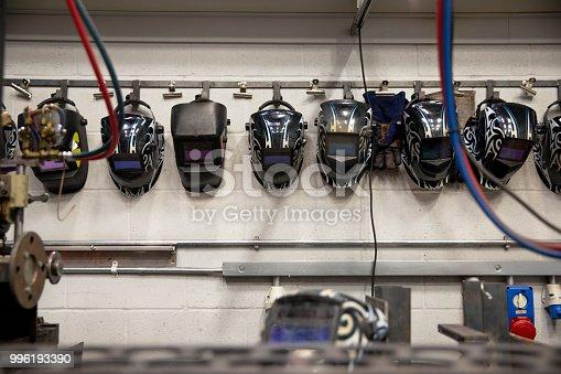Engineering welding masks hang in a row on a wall.