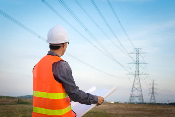 Engineering worker checking location site near to High voltage tower. stock photo