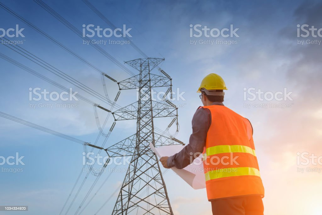 Engineering working on high-voltage tower Engineering working on high-voltage tower,Check the information on paper at sunset background Asian and Indian Ethnicities Stock Photo