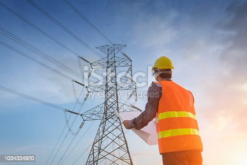 Engineering working on high-voltage tower,Check the information on paper at sunset background