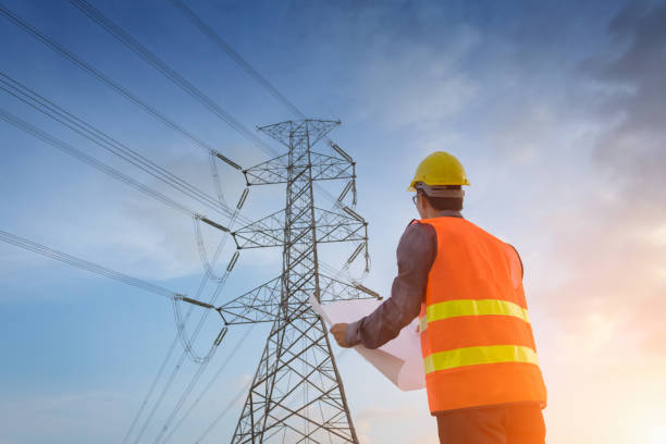 Engineering working on high-voltage tower stock photo